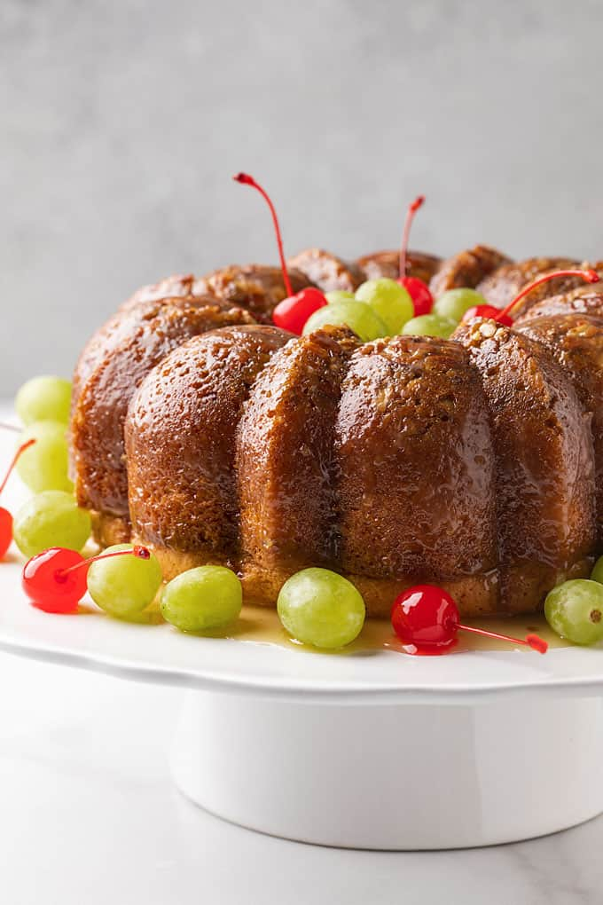 A rum bundt cake on a white cake stand garnished with green grapes and maraschino cherries