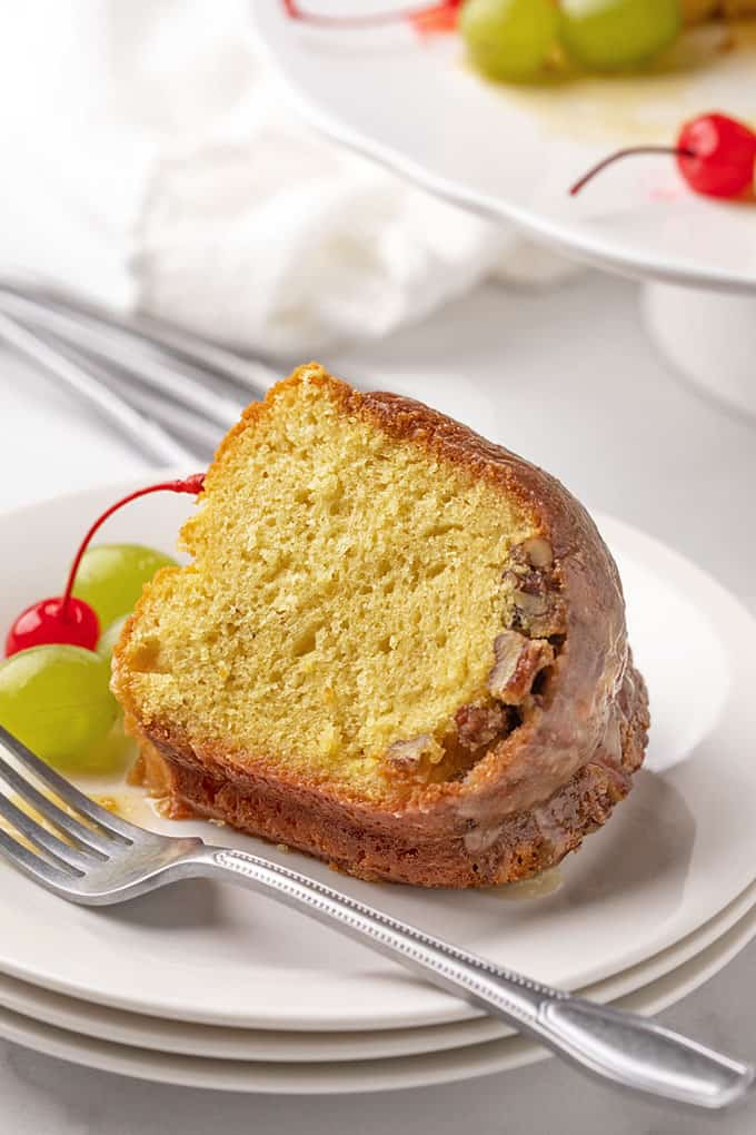A slice of Bacardi rum cake on a white plate with a fork.