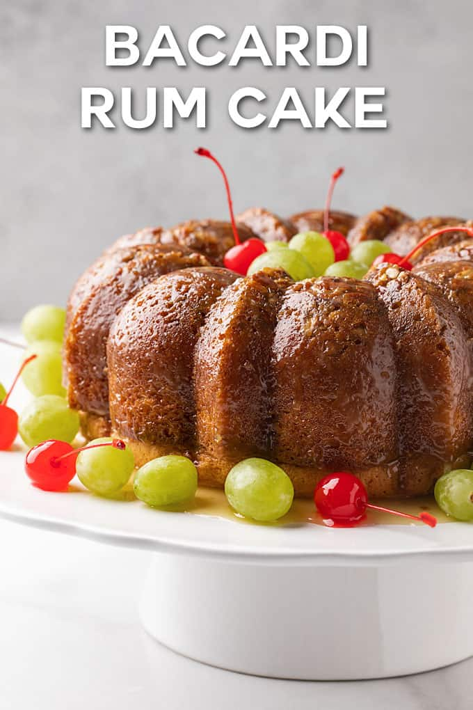 A rum bundt cake with cherries and green grapes on a white cake platter.