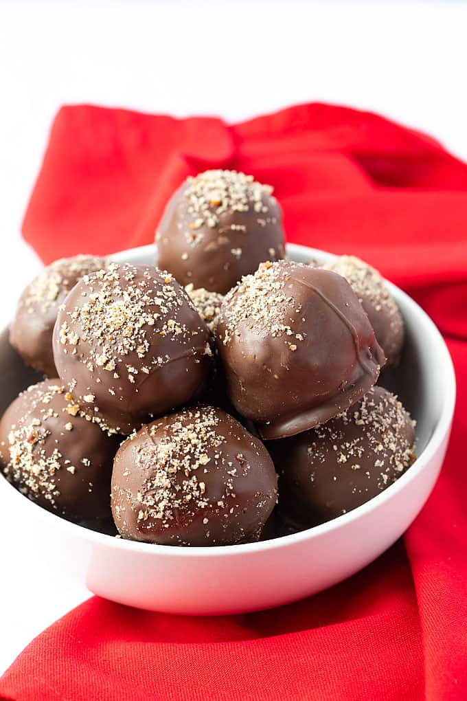 A white bowl of chocolate peanut butter balls beside a red napkin.