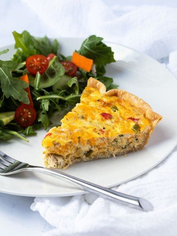 A slice of crab quiche and a garden salad on a white plate with a fork.