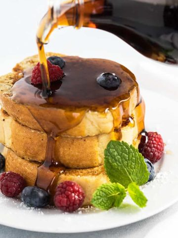 Syrup being poured over a stack of French toast on a white plate.