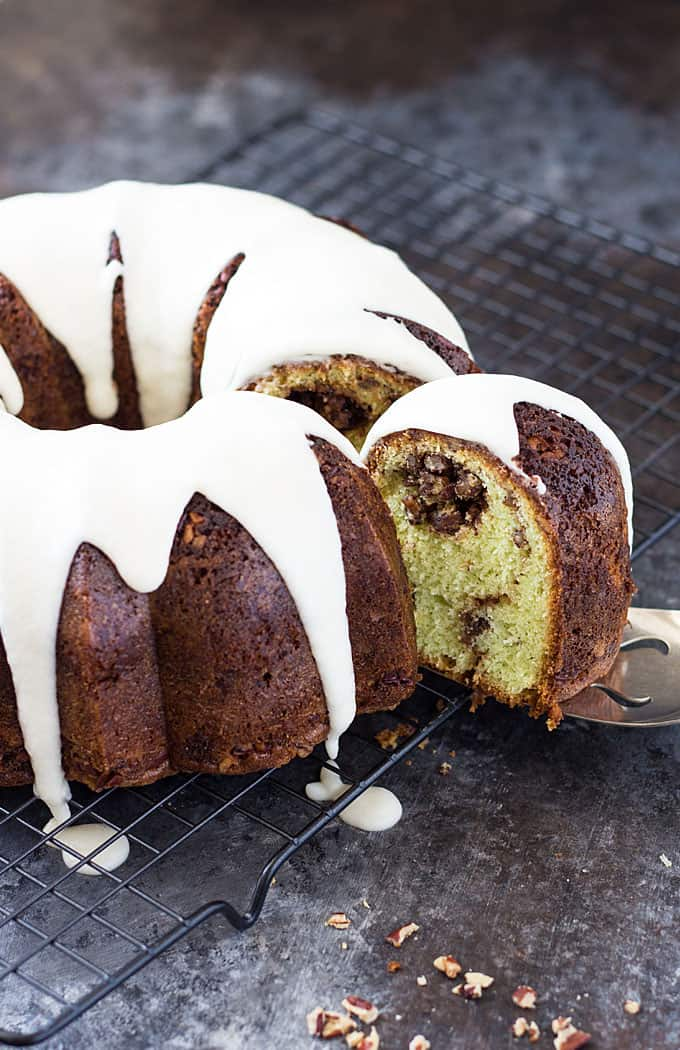 A pistachio bundt cake with a slice being removed on a baking rack.