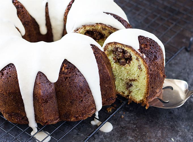 A slice of cake being removed from a bundt cake on a baking rack.
