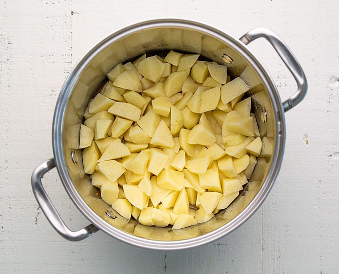 Overhead view of cut potatoes in a stainless pot.