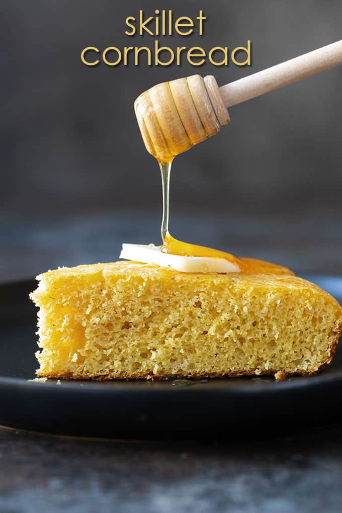 A slice of cornbread on a black plate topped with a pat of butter. A honey dipper is pouring honey on top. Overlay text at top of image.