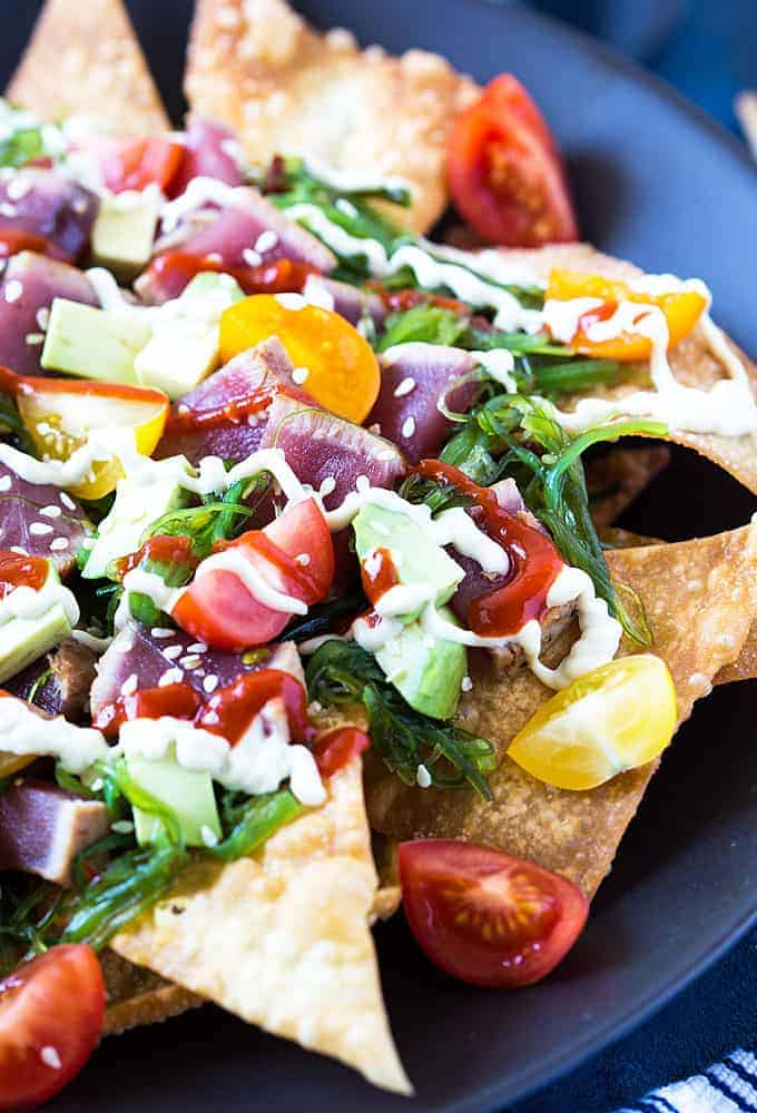 Tuna Nachos - Fried wontons topped with seaweed salad, seared tuna, tomatoes, avocado, sesame seeds and drizzled with wasabi mayo and sriracha.
