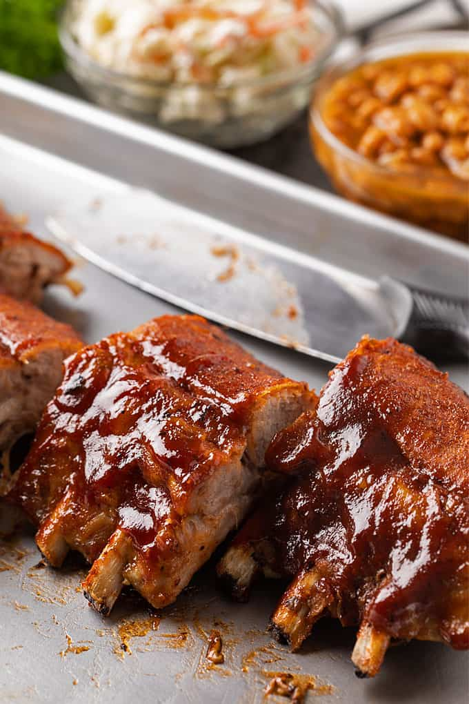 Baked pork ribs on a baking sheet with a bowl of coleslaw and a bowl of baked beans in the background