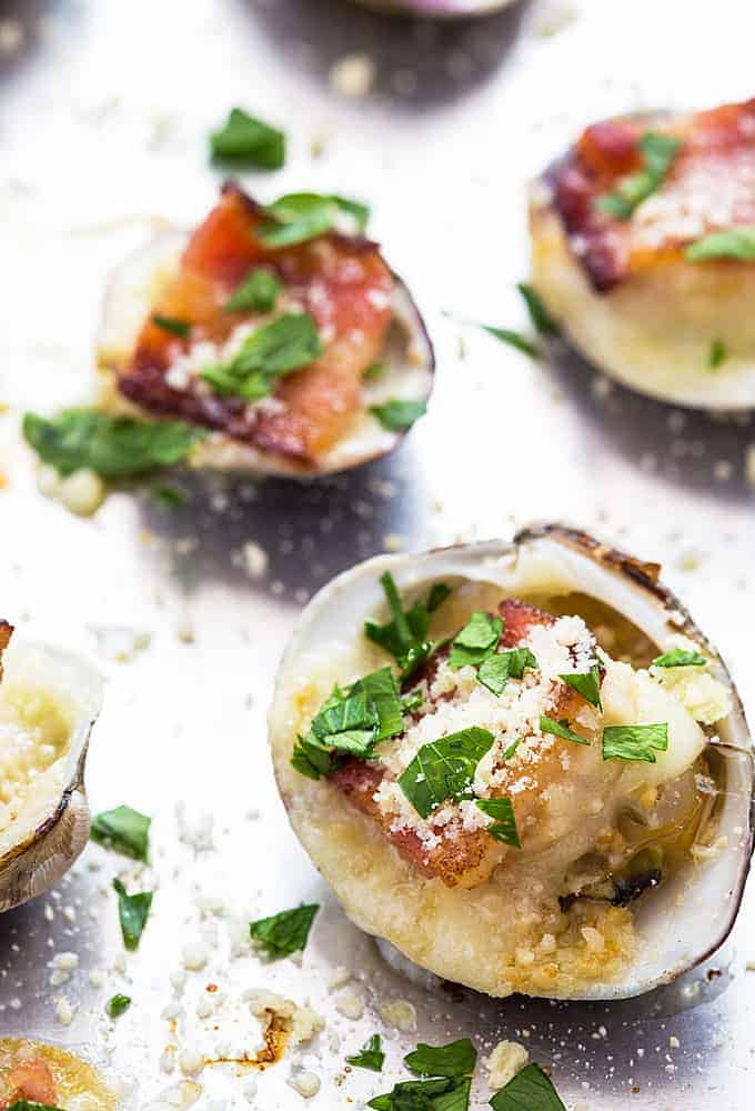 Clams casino garnished with fresh parsley on a baking sheet