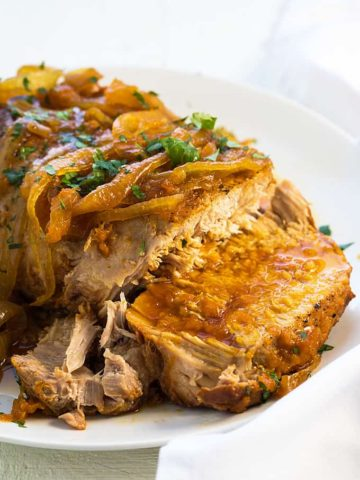 A sliced pork roast topped with onions and apricot glaze on a white platter.