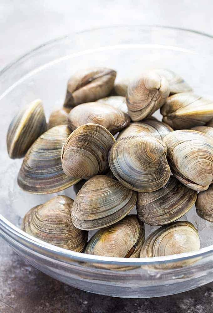 Fresh little neck clams in a clear glass bowl.