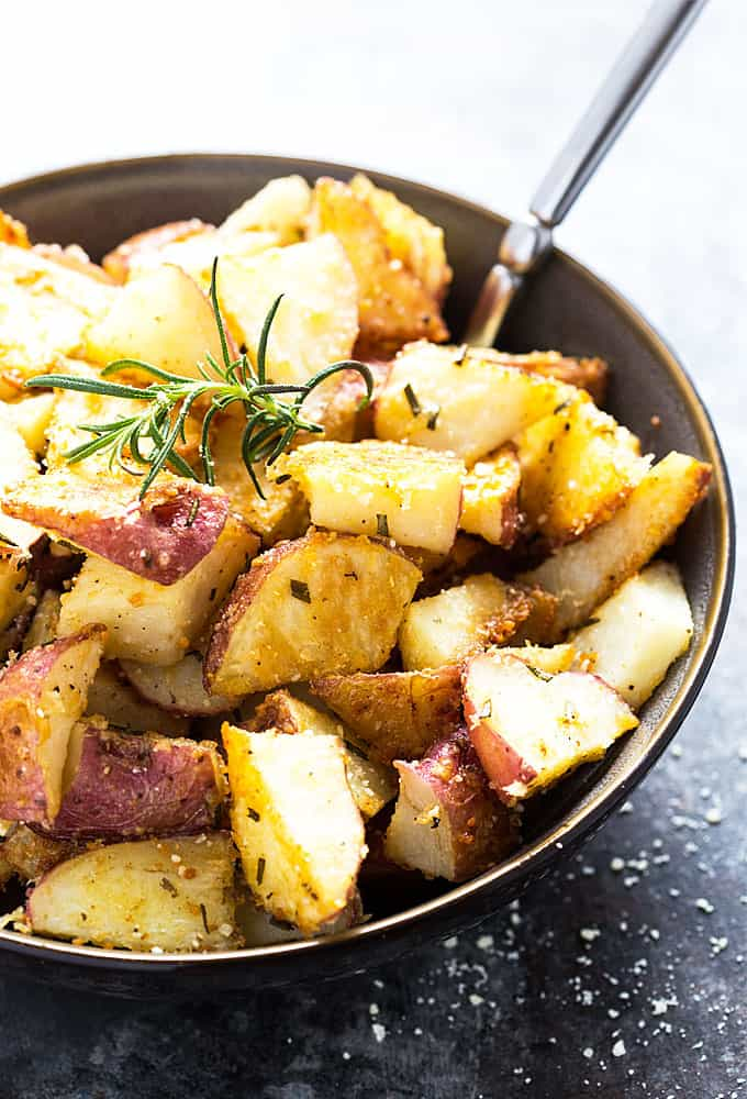 A closeup of roasted potatoes in a bowl with a spoon.