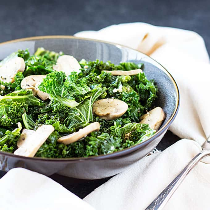 Front view of kale and mushrooms in a gray bowl beside a napkin and fork.