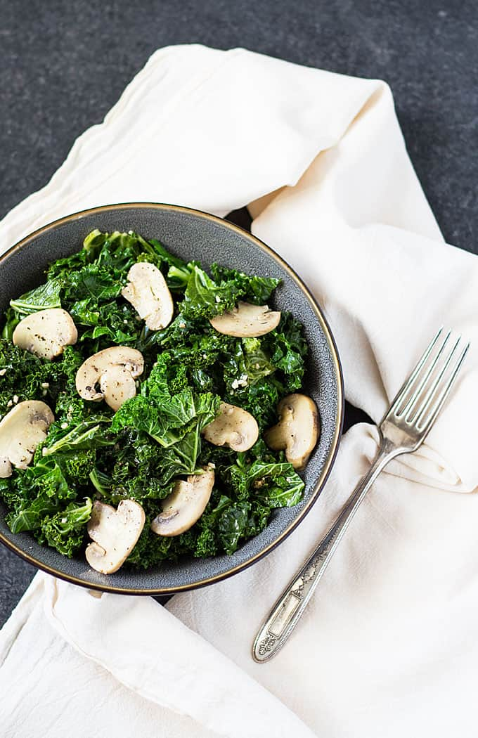Overhead view of kale and mushrooms in a gray bowl beside a fork and napkin.