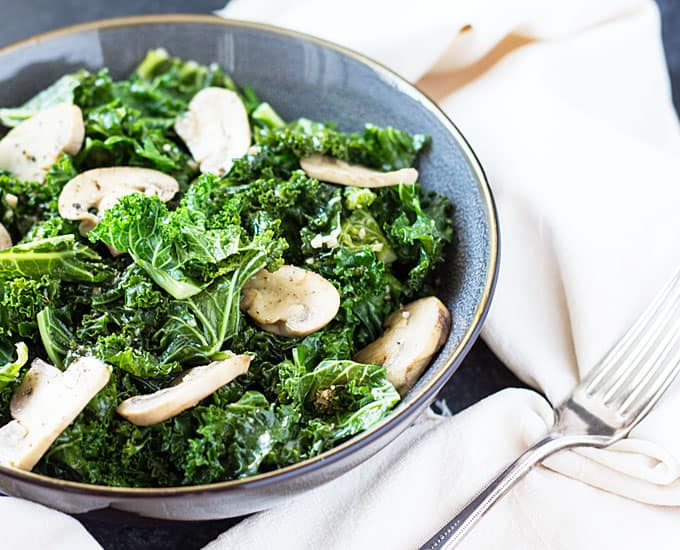 Kale and mushrooms in a gray bowl beside a napkin and fork.