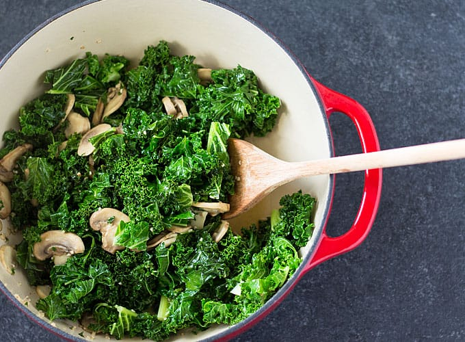 Overhead view of kale and mushrooms in a red dutch oven with a wooden spoon.