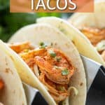 """Tacos in a taco holder. Overlay text reads """"shrimp tacos""""."""
