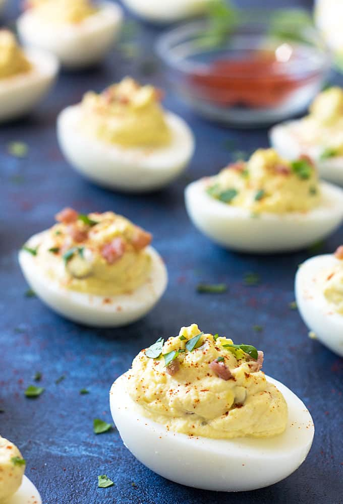 Front view of deviled eggs on a blue surface.