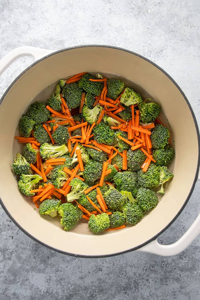 Fresh broccoli florets and julienned carrots in a dutch oven