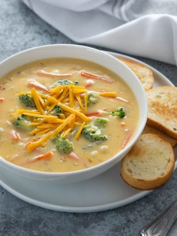 Broccoli cheese soup in a white bowl on a white plate with French Bread