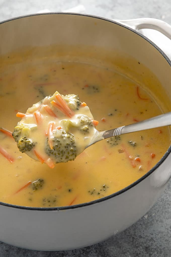Homemade broccoli cheese soup in a dutch oven with a ladle