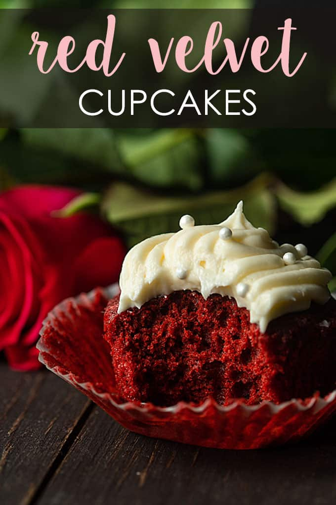 A red velvet cupcake with cream cheese frosting that has been bitten into beside a red long-stemmed rose.