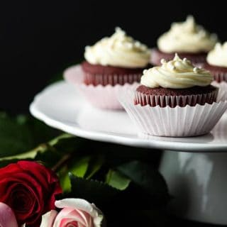 Red Velvet Cupcakes with cream cheese frosting on a cake stand with long-stemmed red and pink roses.