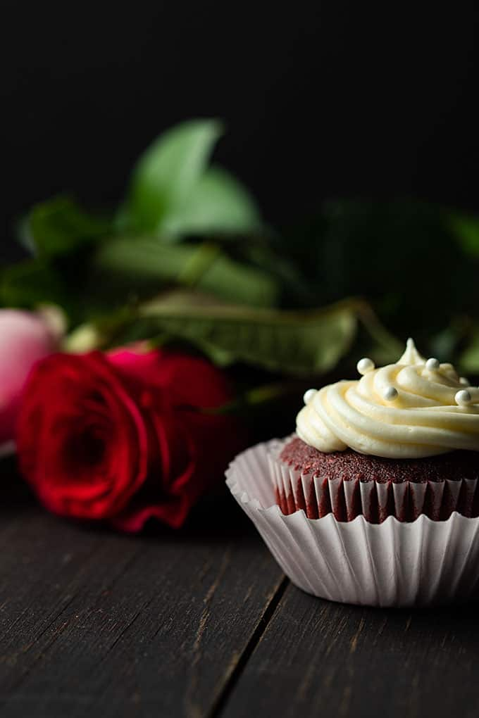 Red Velvet Cupcakes with cream cheese frosting on a white cake stand with long-stemmed red and pink roses.