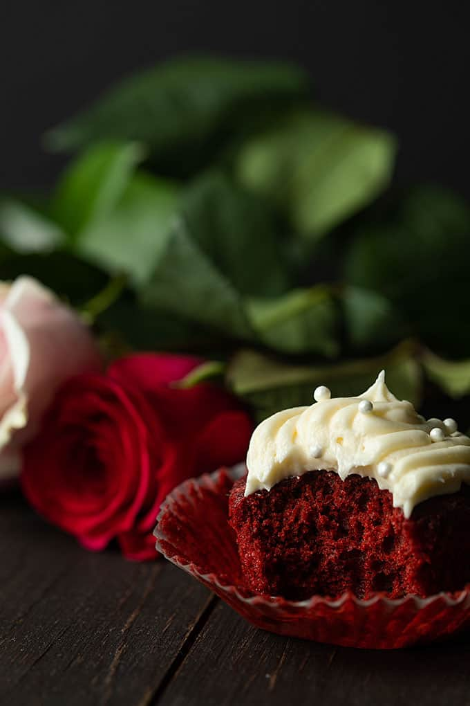 A red velvet cupcake with cream cheese frosting that has been bitten beside red and pink long-stemmed roses.