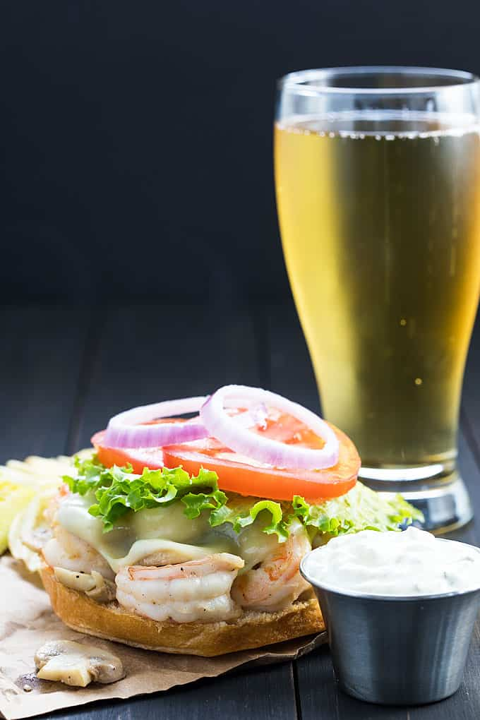 An open-faced sauteed shrimp burger topped with lettuce, tomato and onion.