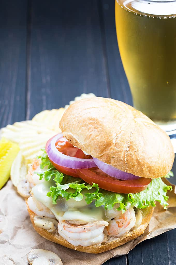Closeup view of a shrimp burger by a cup of tartar sauce and a beer.