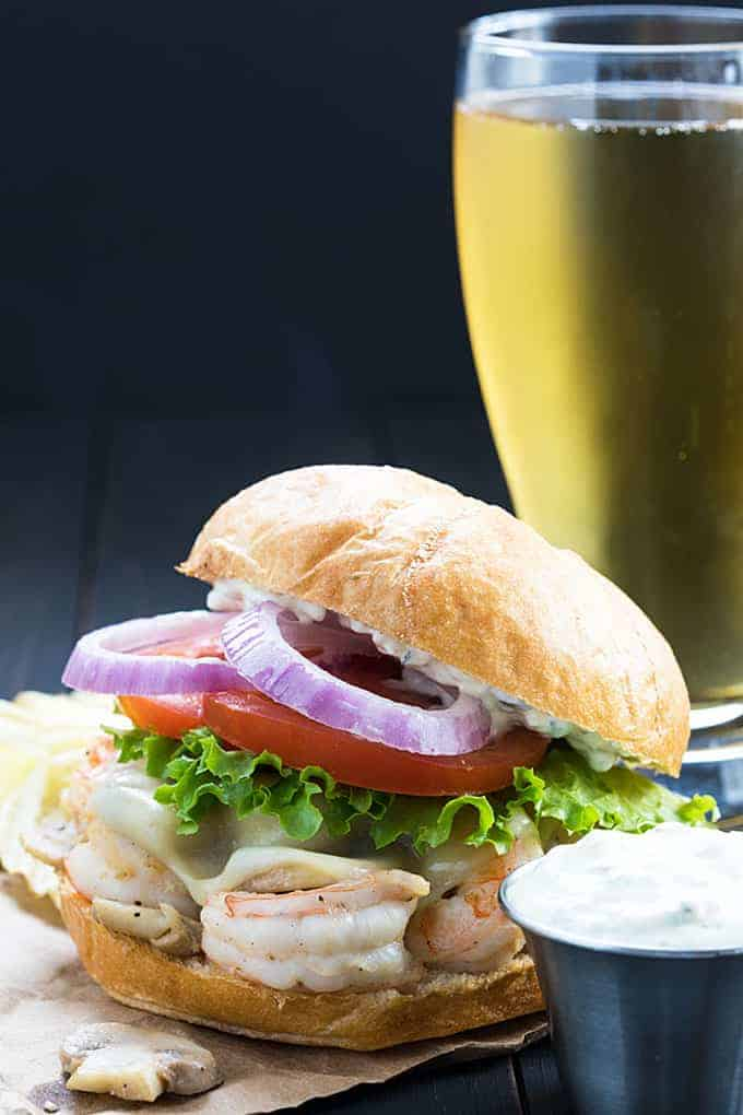 Front view of a shrimp burger with a glass of beer in the background.