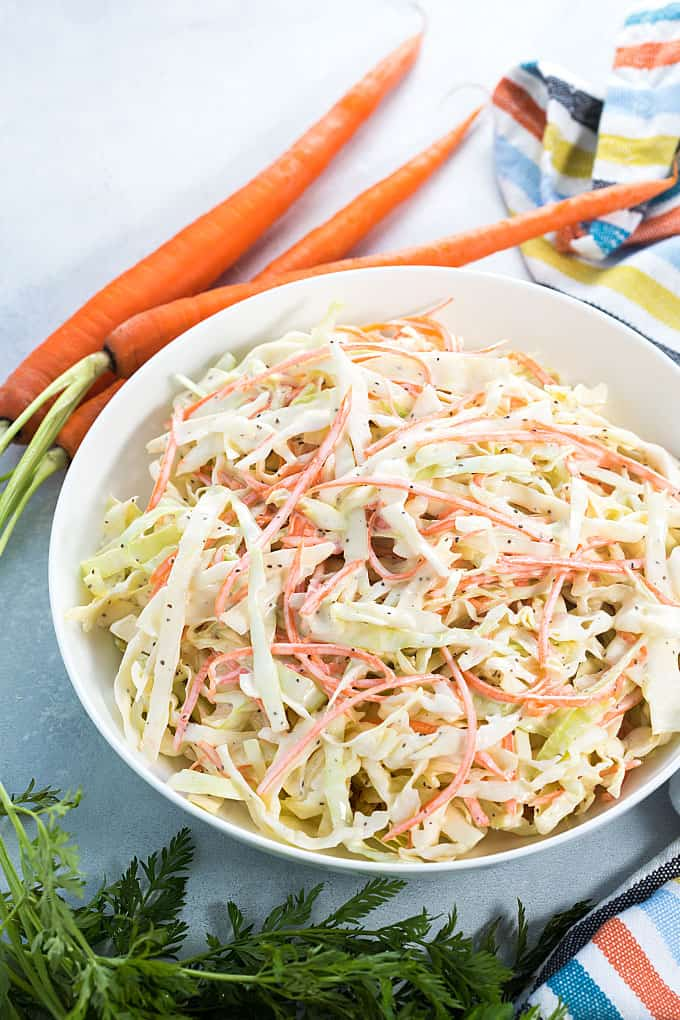 A white bowl of creamy cabbage coleslaw with carrots beside a striped napkin.