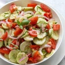 Overhead view of Cucumber tomato salad in a round white serving bowl
