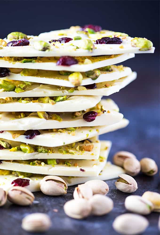 Front closeup view of a stack of chocolate bark by pistachios in their shell.