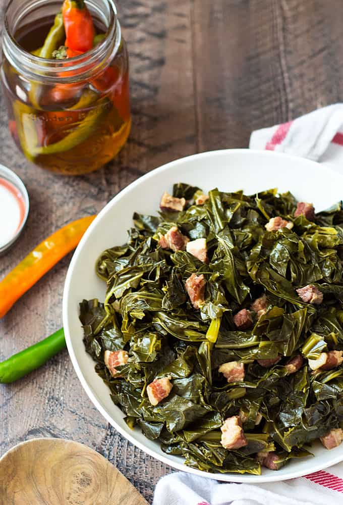 Overhead view of collard greens with ham in a white bowl beside a jar of pepper vinegar.