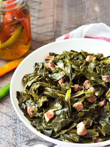 A white bowl of collard greens with pork pieces by a jar of vinegar.