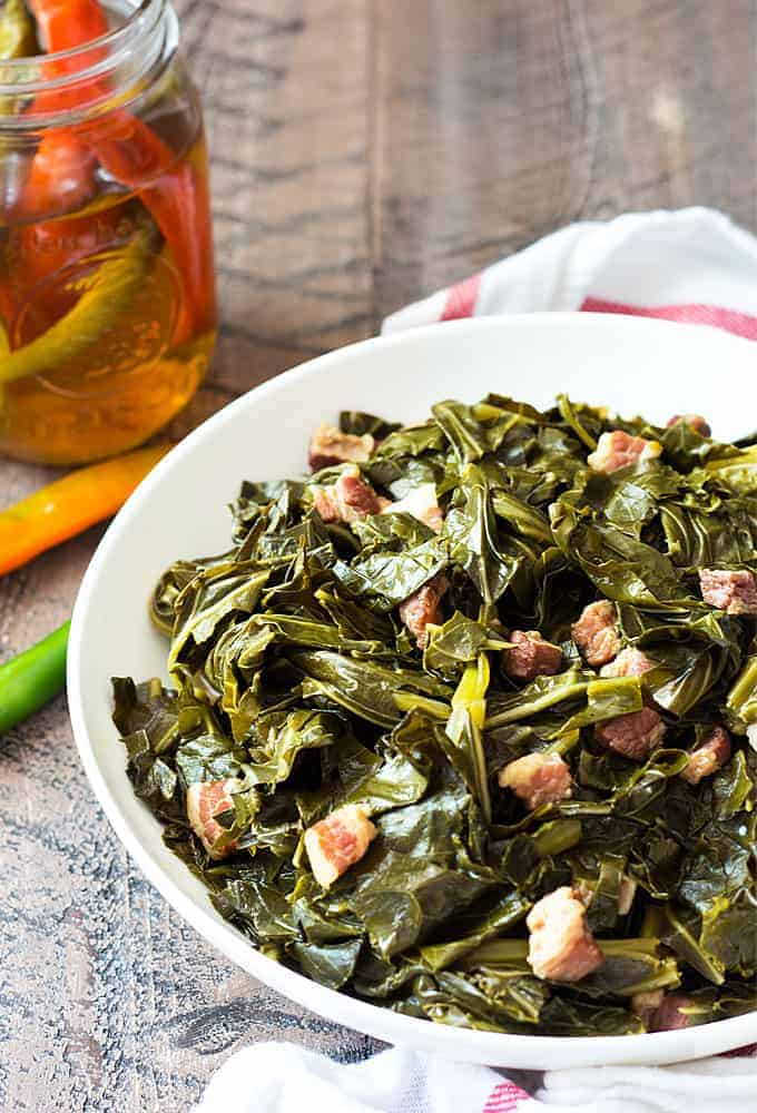 Southern style collard greens in a white bowl on a wood surface.