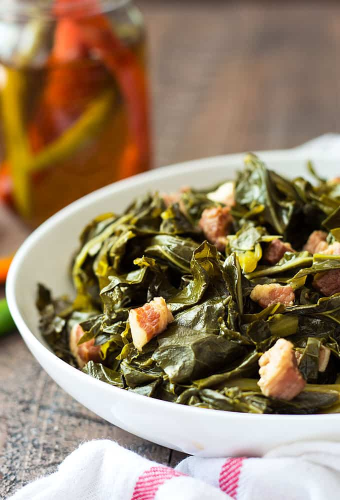 Front view of collards with salt pork pieces in a white bowl.