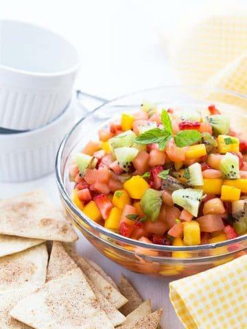 A bowl of fruit salsa beside cinnamon chips.