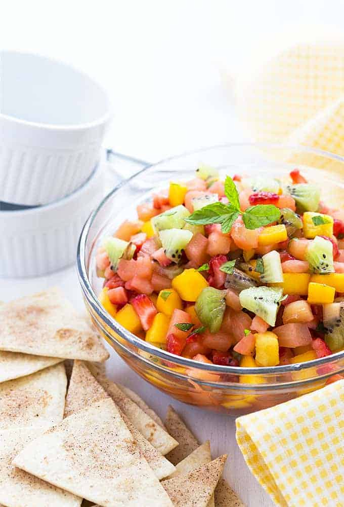 A bowl of fruit salsa beside cinnamon chips.