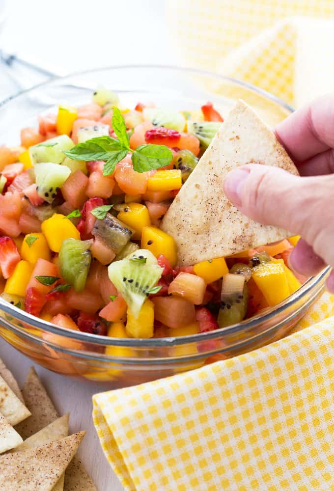 A hand dipping a chip into a bowl of fruit salsa.