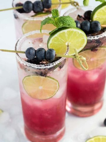 Three blueberry mojitos garnished with blueberries, lime and mint.