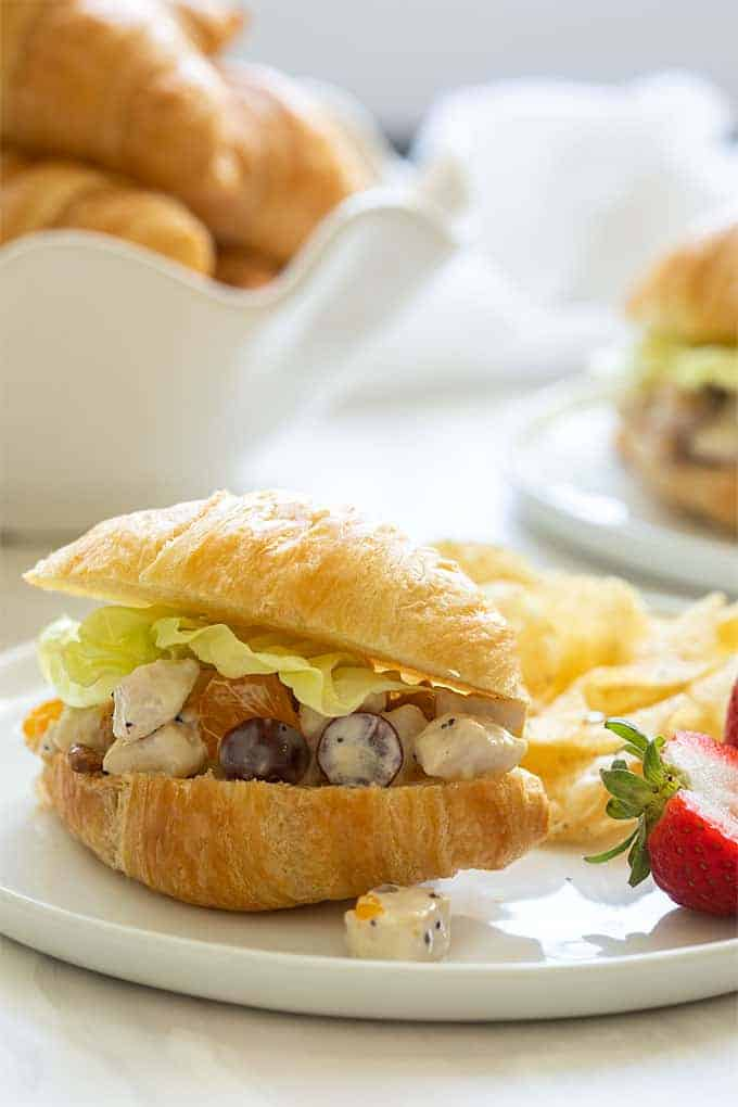 Summer chicken salad on a croissant with fresh strawberries and potato chips on a round white plate