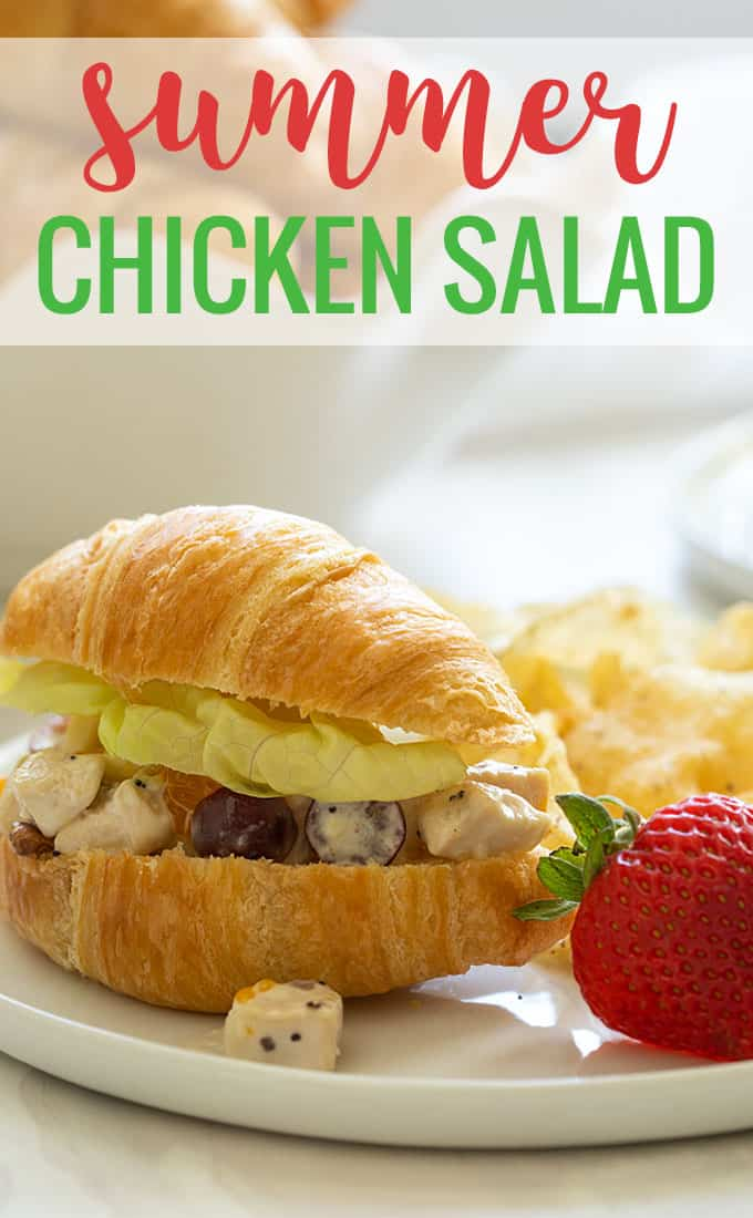 A chicken salad sandwich made with croissants on a white plate.