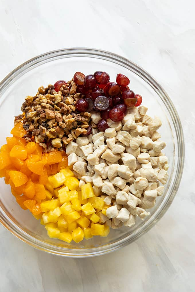Cubed cooked chicken, chopped pineapple, mandarin oranges, grapes and walnuts in a glass bowl for chicken salad recipe