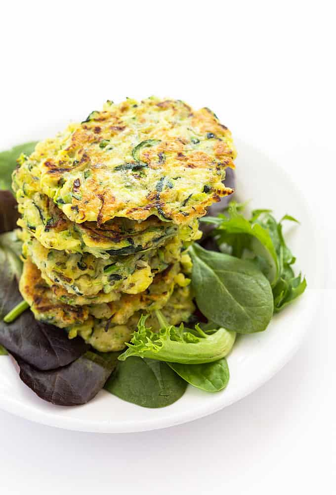 Overhead view of stacked fritters with mixed greens on a white plate.