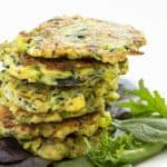 A stack of zucchini fritters with mixed greens on a white plate.