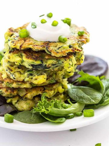 A stack of zucchini fritters topped with sour cream and green onions on a white plate.
