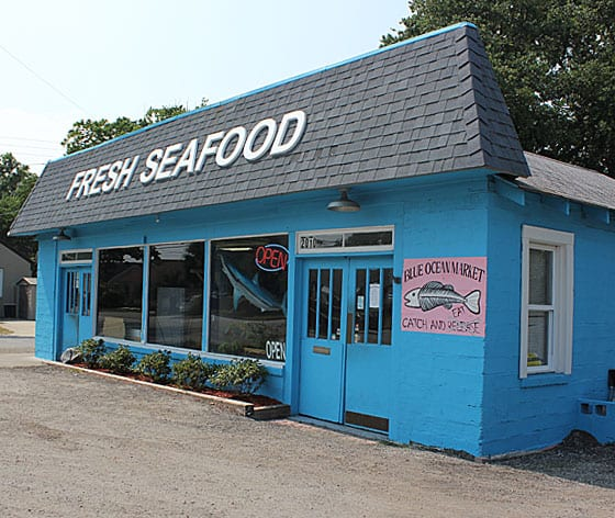 The outside view of a seafood market painted blue with 3 big windows in front.